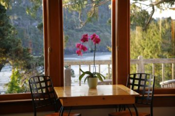 Pacific room - Table with Orchid as centerpiece - View of trees and sea beyond the railing of the porch
