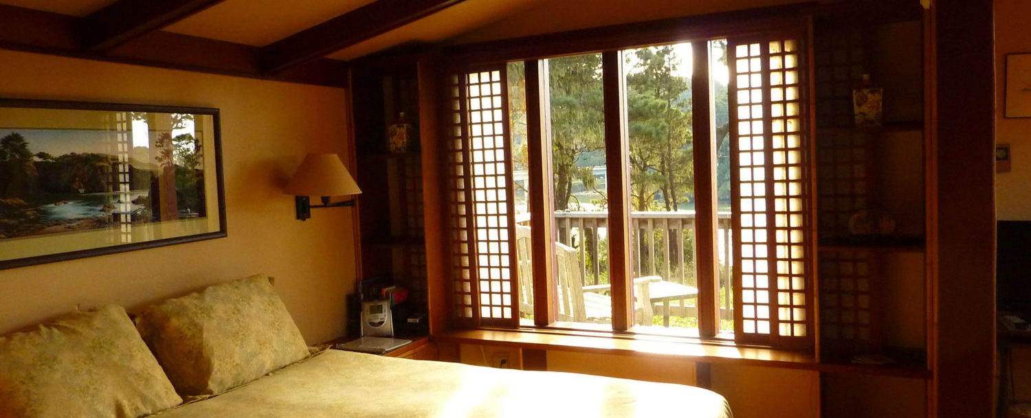 Cove room - view out the windows of the bedroom (trees and further on the sea)