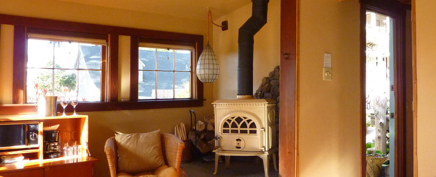 Cove room - view of stove, chair, bar, square windows and door