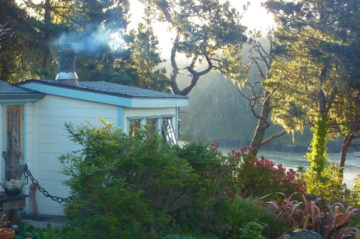 Cove room with smoke coming out the chimney - with view of sea, trees and flowering garden