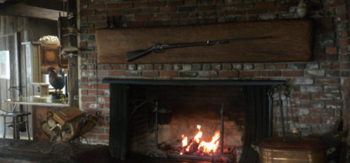 Large Fireplace in the Dolphin House - rifle mounted above it on the brick, firewood beside it and pot on the other side