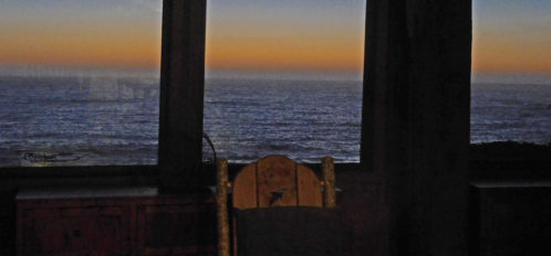 Rocking chair with sunset over the sea in the windows behind it