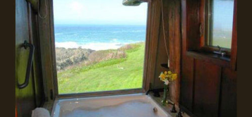 Soaking tub with a view of the cliffside and ocean