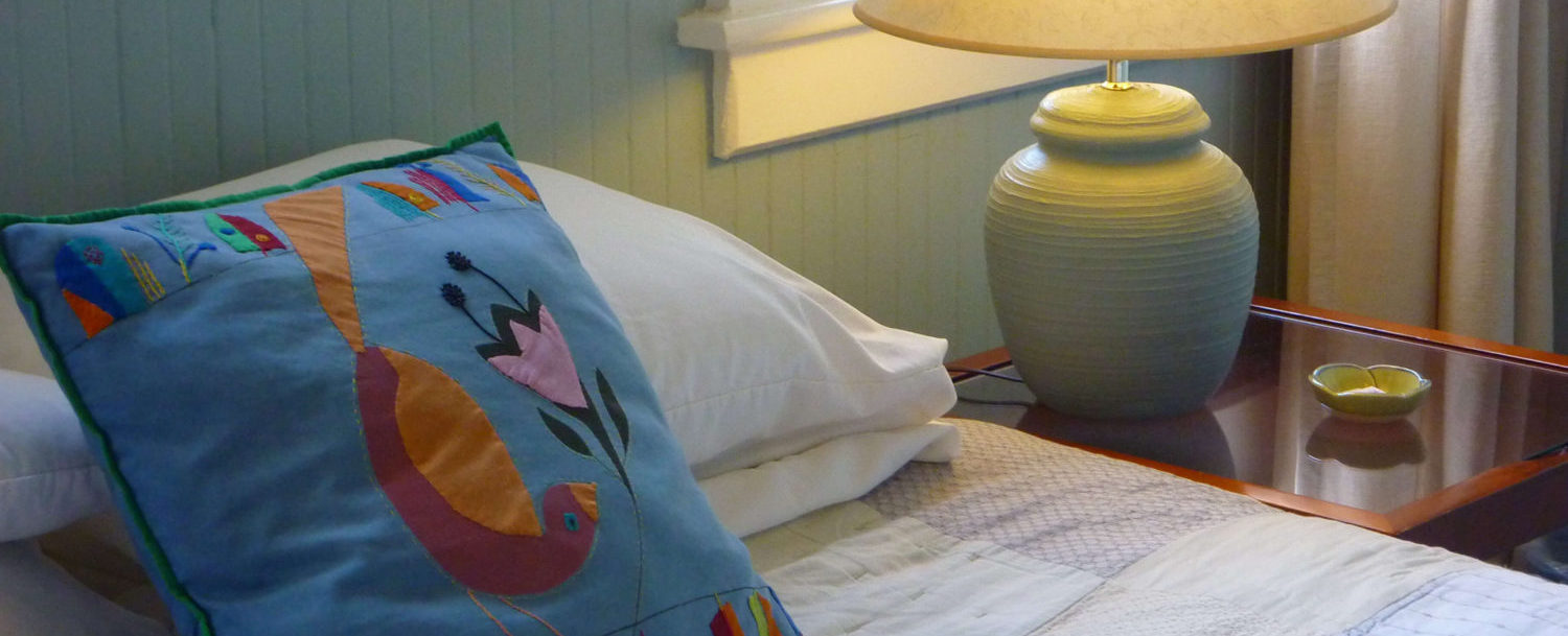 West Room Pillow, bed, nightstand and lamp close-up